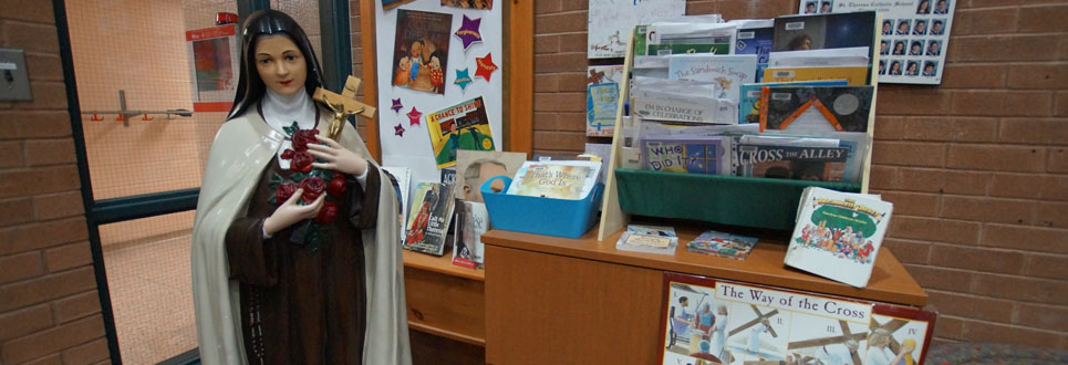 St. Theresa statue beside an desk with educational religious materials.